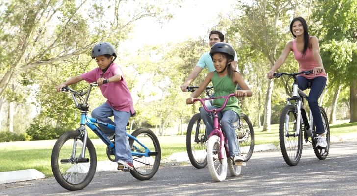 A mother and father riding bikes in the park with their little son and daughter