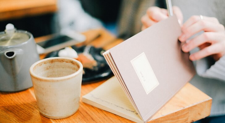 A hand opening a notepad holding a pen ready to write in a café with a cup of coffee
